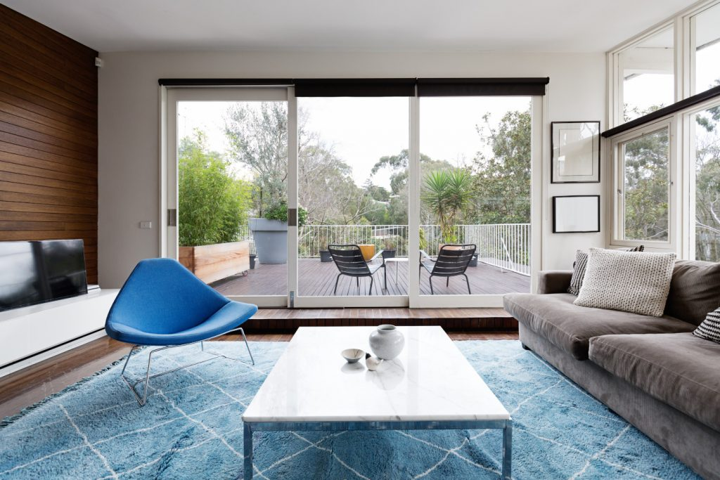 Luxury scandinavian styled living room with outlook to terrace and gum trees