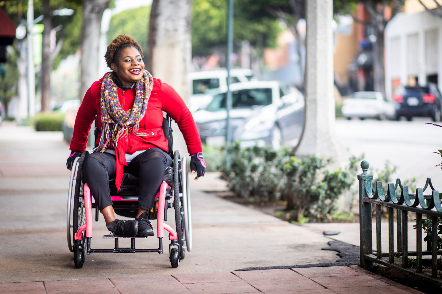 A young black disabled woman with a wheelchair and a bright colored sweater and her Asian friend walk around the city.
