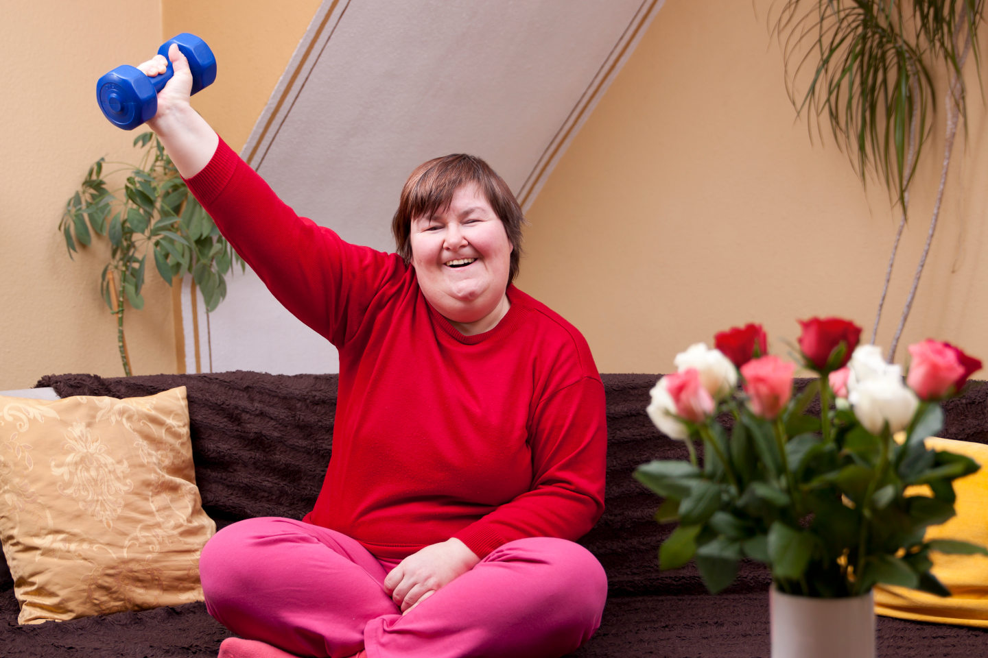 Mentally disabled woman shows her strength with a dumbbell. She has MS.