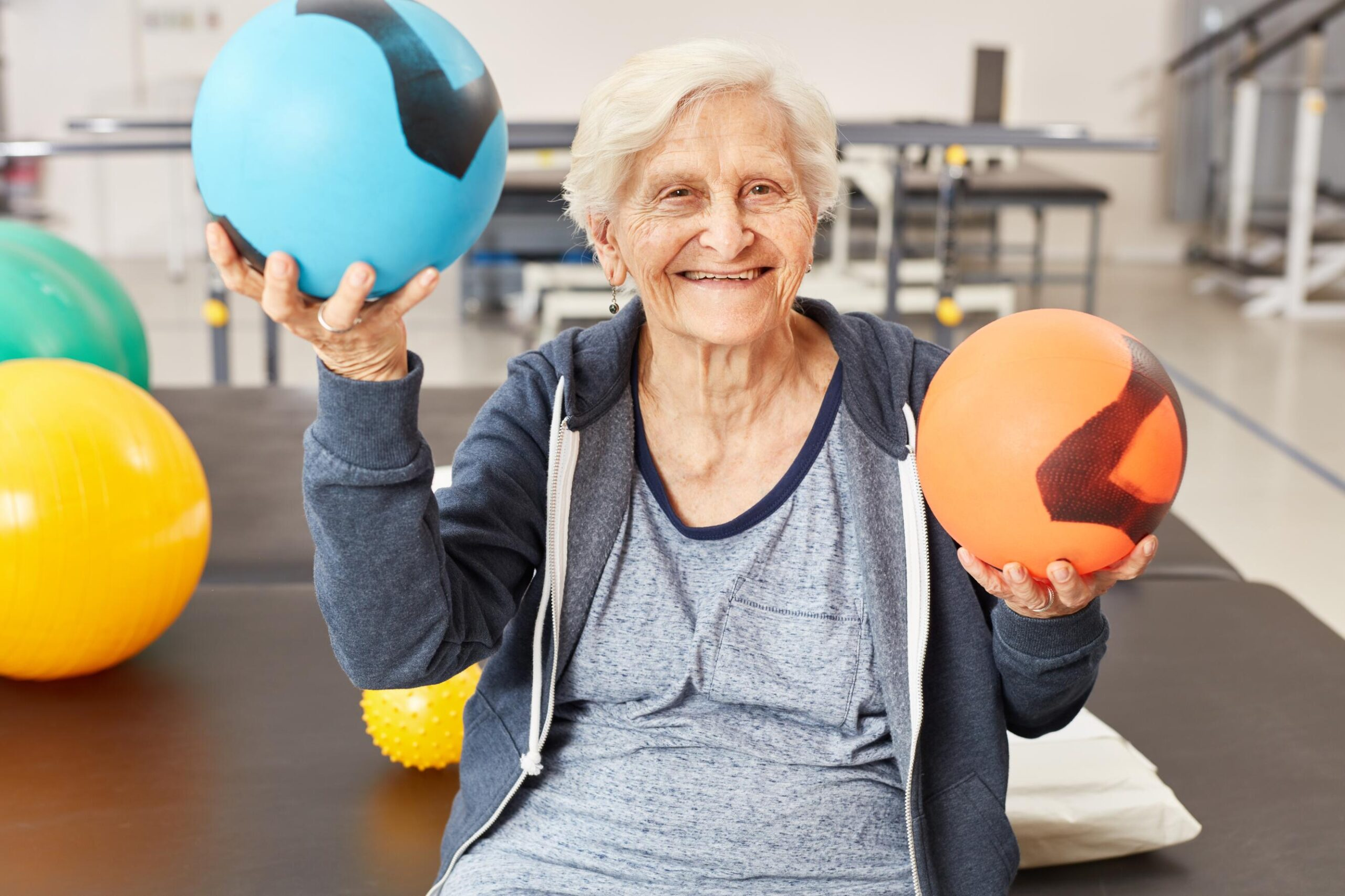 Senior woman balances balls as exercise for coordination in occupational therapy