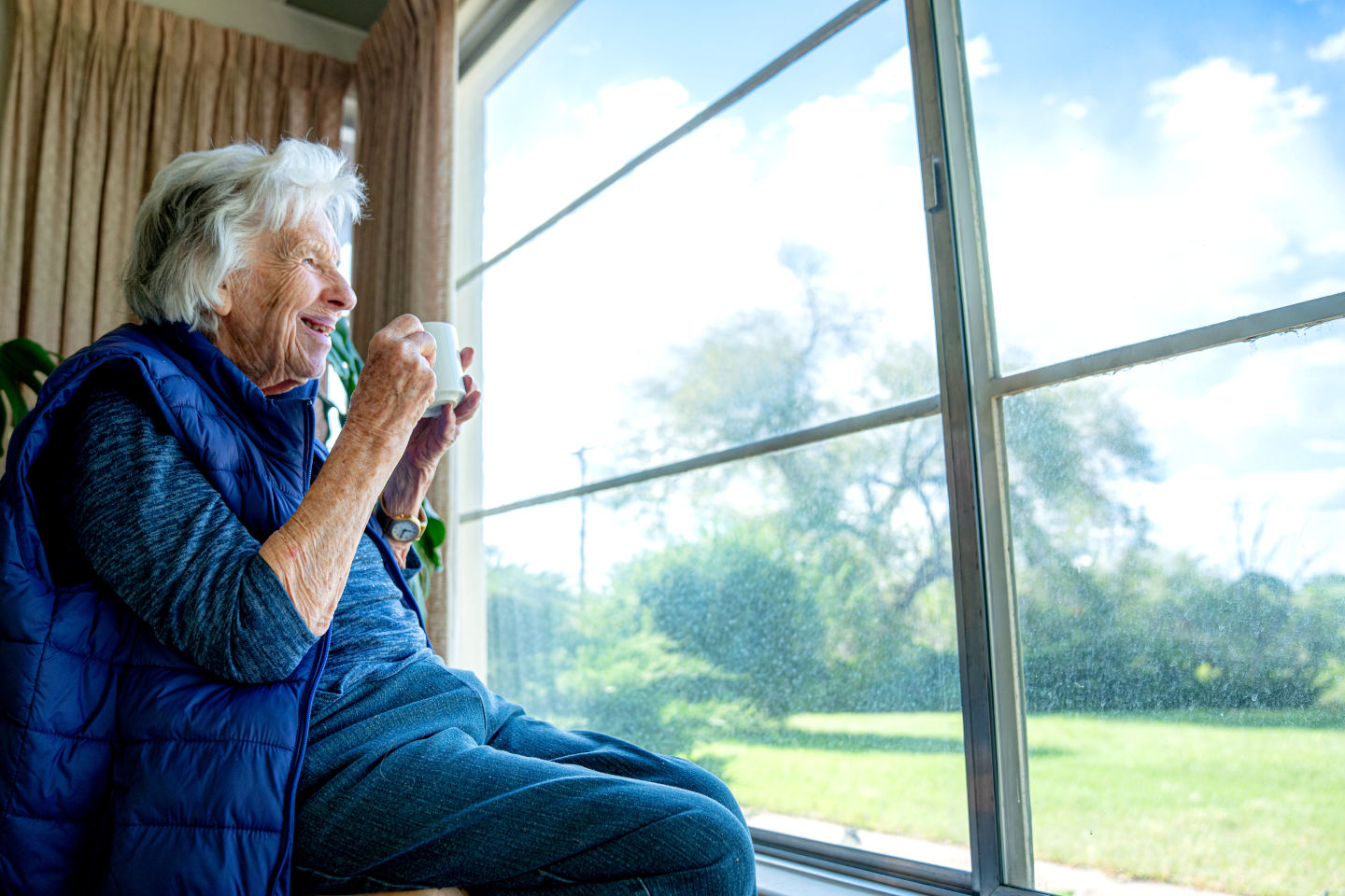 Elderly Senior Caucasian Woman Indoors Holding Coffee or Tea in a Mug and Looking Out the Window Enjoying the View in the Summer