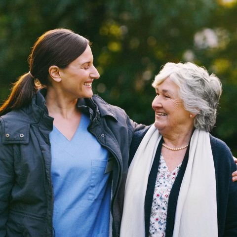 Shot of a senior woman and young nurse going for a walk in a garden