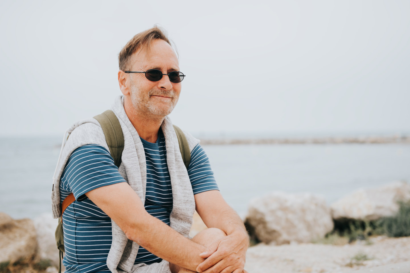 Man enjoying summer vacation by the sea, wearing stripe nautical t-shirt and backpack. Image taken in Saintes-Maries-de-la-Mer, capital of Camargue, south of France