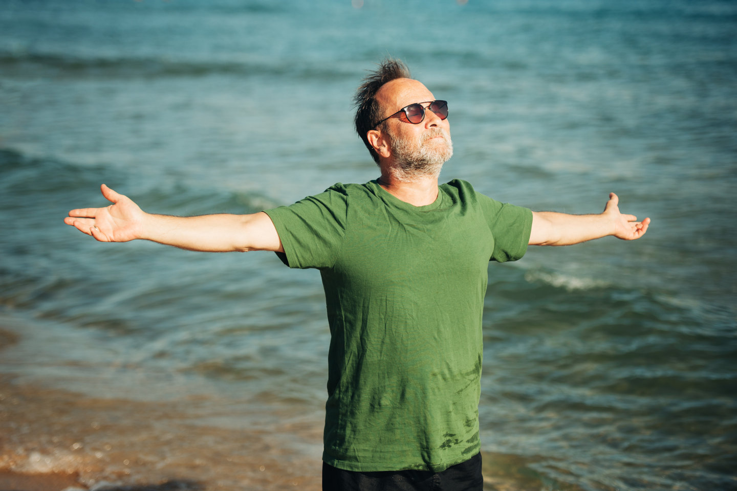 Portrait of happy middle age man enjoying nice sunny day on the beach, wearing green t-shirt and sunglasses, arms wide open