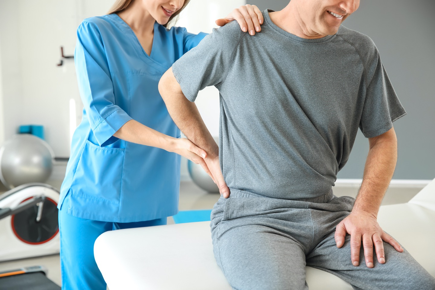 Physiotherapist working with mature patient in rehabilitation center treating a person with back pain
