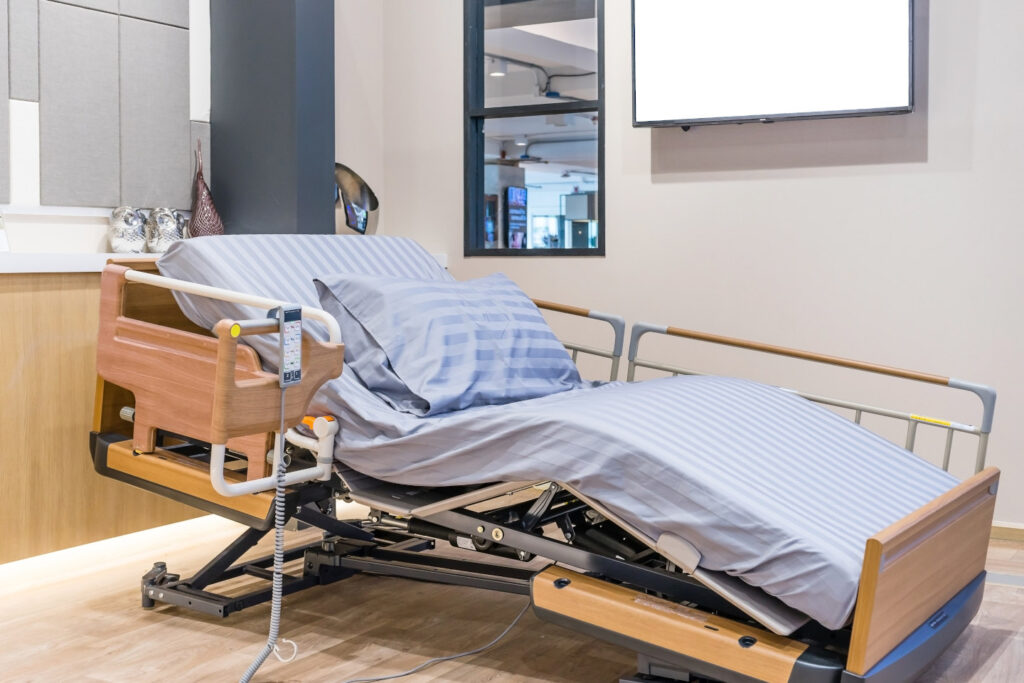 Electrical adjustable patient bed in hospital room. Technology of medical and hospital services.