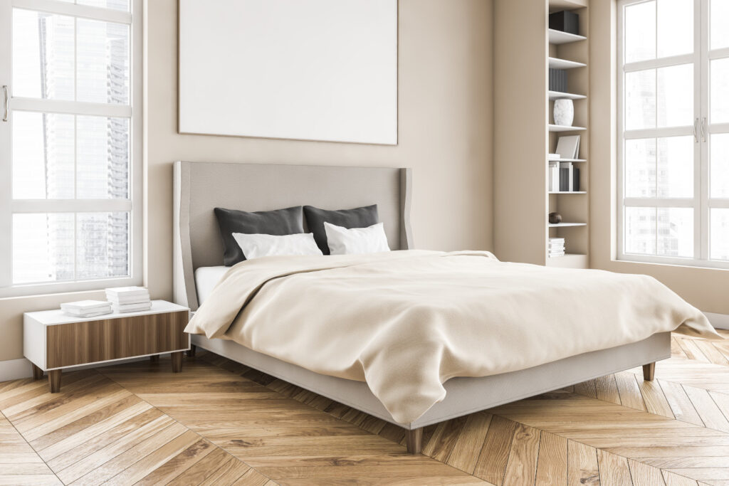 Wooden living room with mockup frame over the bed with linens on parquet floor, side view. Light brown minimalist bedroom with shelves and books. Windows with city view, no people 3D rendering